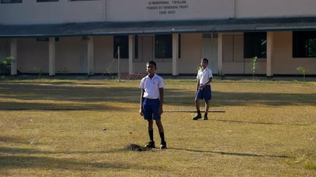 schoolyard : ColomboSRI LANKA - APRIL 05 2019: Sinhalese boys in blue shorts and white shirts stand on playground against school building slow motion. Concept sport and competition on April 05 in Colombo