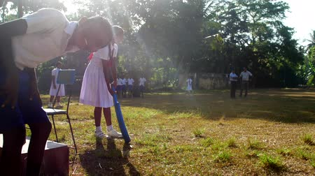 školák : ColomboSRI LANKA - APRIL 05 2019: Young lady in white dress silhouette holds blue cricket bat with funny schoolboy on foreground slow motion. Concept gender equality on April 05 in Colombo Dostupné videozáznamy