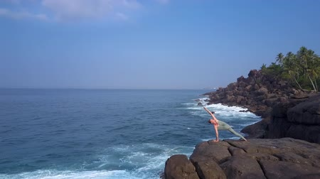 harcos : slim and flexible woman practices warrior yoga asana standing on large stone by blue ocean bird eye view