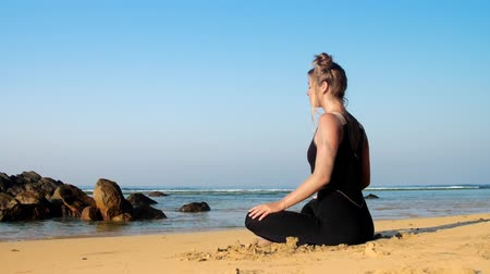 melegítőben : sporty girl in black tracksuit meditates on yellow sandy beach against endless blue ocean and clear sky extreme slow motion. Concept yoga sport healthy lifestyle Stock mozgókép
