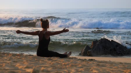 dres : woman in black tracksuit does breathing exercises in early morning on ocean coast against beautiful azure waves slow motion. Concept sport healthy lifestyle, seascape travel