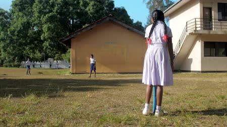schoolyard : ColomboSRI LANKA - APRIL 05 2019: Sinhalese girl in white dress holds blue cricket bat against schoolboys in autumn slow motion. Concept gender equality and healthy lifestyle on April 05 in Colombo
