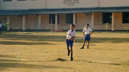 školák : ColomboSRI LANKA - APRIL 05 2019: Sinhalese schoolboy throws cricket ball on playground with trees shadows against building slow motion. Concept sport and competition on April 05 in Colombo Dostupné videozáznamy
