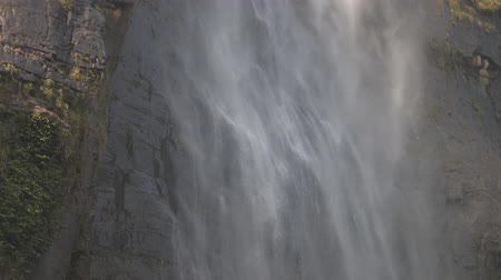 low angle shot : wonderful white foaming waterfall from rocky cliff with green grass under blue sky slow motion low angle shot. Concept nature conservation Stock Footage
