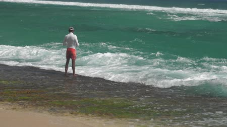 zadnice : MIRISASRI LANKA - APRIL 04 2019: Asian man in white turtleneck stands in picturesque azure sea waves on sunny day backside view extreme slow motion. Concept travel vacation on April 04 in Mirisa Dostupné videozáznamy