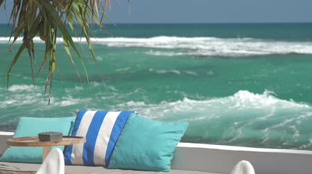 clear the table : comfortable rest place with pillows on bench and table by picturesque ocean at tropical resort slow motion. Concept travel vacation Stock Footage