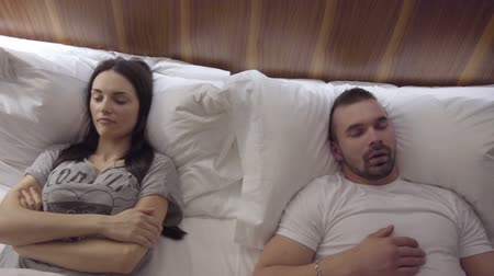 badstoffen : Snooring man en boze vrouw in bed Stockvideo