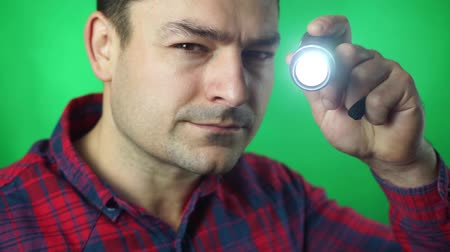 lodówka : man works flashlight to find the problem green screen background