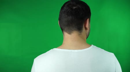 young handsome bearded man looks around - shot on back (man looks to screen) - green screen - studio Vídeos