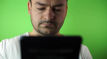 Young man with tablet computer green screen background