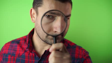 Enlarged eye of tax inspector looking through magnifying glass, inspecting offshore company financial papers, documents and reports. green screen background Vídeos