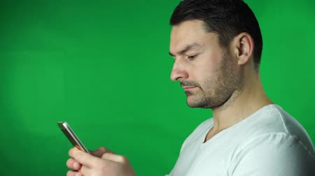 Young man using smartphone green screen background Vídeos
