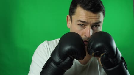 Angry anonymous businessman with a paper bag on his head and threatening someone while wearing boxing gloves. Shot green screen background