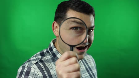 zvětšit : business man holding magnifying glass green screen is amazed background Dostupné videozáznamy