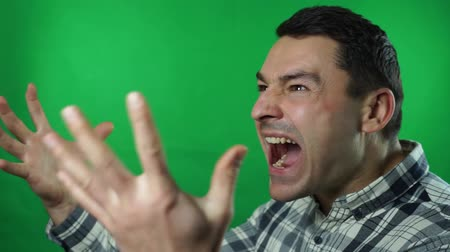 Angry crazy angry man screaming against green screen background Vídeos