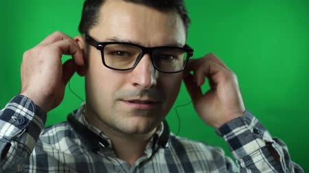 man listening music in headphones isolated on green screen background