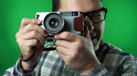 Man taking pictures with an old camera. green screen background Vídeos