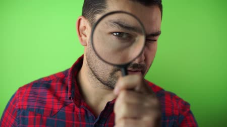 investigator looking with magnifying glass green screen background Vídeos