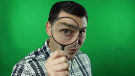 man in a suit looking through a magnifying glass is amazed green screen background Vídeos