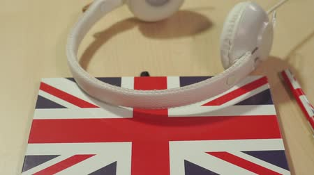 learning english courses logo concept with british flag and headphones. English school logotype Vídeos