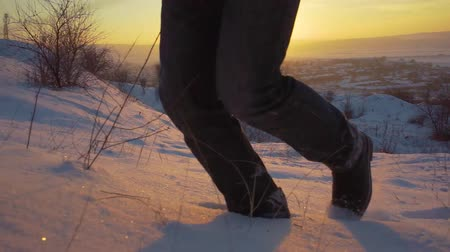 lose up of feet walking in snow landscape. winter hiking journey adventure background