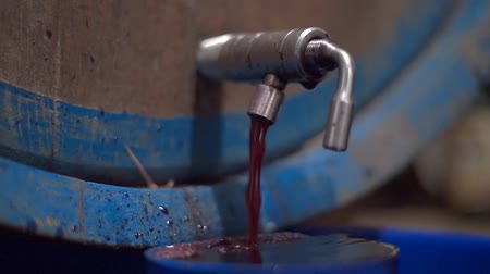 red wine flows out from tap of a tank inside a wine cellar