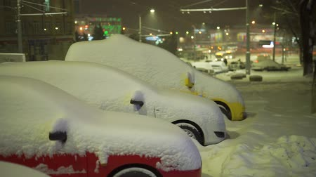 Cars under street lamps covered in deep snow winte Vídeos
