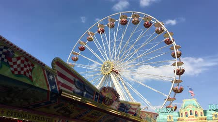 nárazník : BERLIN - JUNE 3, 2017: Ferris Wheel at German Fun Fair turning - Wide Shot blue sky Dostupné videozáznamy