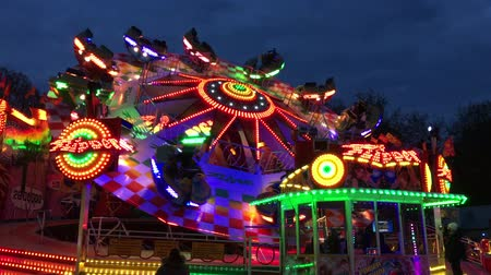 targi : BERLIN, Germany - JUNE 3, 2017: Funfair Ride (Flea Market) Flipper at German Fun Fair (Fair) at night - Wide Shot - 4K