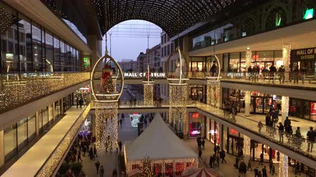 průchod : Berlin, Germany - December 16, 2018: Shopping Mall of Berlin decorated for Christmas, busy with many Shoppers and illuminated with thousands of lights - late afternoon  evening Dostupné videozáznamy