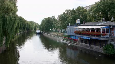 zoolojik : Berlin, Germany - July 13, 2018: Idyllic Landwehr Canal (Canal) in Kreuzberg with Boats and Swans in the Summer