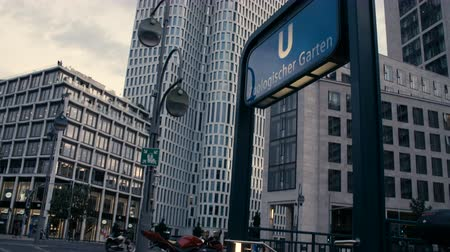 breitscheidplatz : Berlin, Germany - July 13, 2018: Tilt down from Metro (U-Bahn) Sign Zoologischer Garten with Upper West Tower and Zoofenster in Background to Metro Entrance in Charlottenburg. Someone crossing.