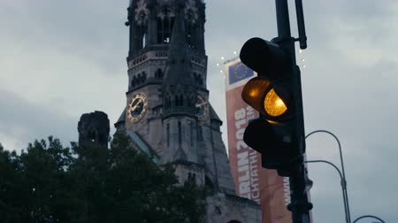 evangelical : Berlin, Germany - July 13, 2018: Traffic light turning red with Kaiser Wilhelm Memorial Church (Gedaechtniskirche) at the background in Berlin Stock Footage