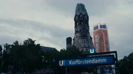 breitscheidplatz : Berlin, Germany - July 13, 2018: Metro (subway) sign Kurfuerstendamm with Kaiser Wilhelm Memorial Church in background. Evening. 4K.