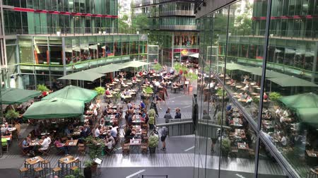 Berlin, Germany - May 25,2018: Crane down over people enjoying restaurants and services at Potsdamer Platz Sony Center