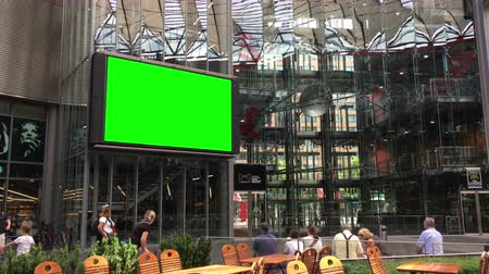 Berlin, Germany - May 25,2018: people watching big screen at Potsdamer Platz with green screen for compositing