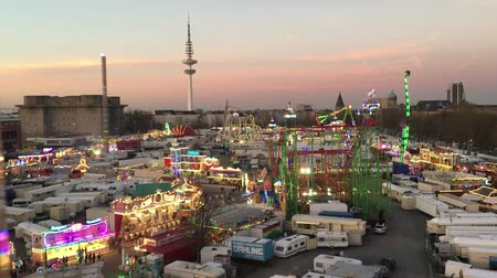 карусель : HAMBURG - March 27, 2017: Wide Birds Eye Shot of large Fun Fair Hamburger Dom from Ferris Wheel with Roller Coaster, Carnival Rides and Hamburg Skyline at dusk