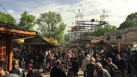 BERLIN - May 1, 2019: Crowded Fun Fair  Carnival with Roller Coaster in sunny spring weather (Kirmes) in Neukölln  Kreuzberg Stock mozgókép