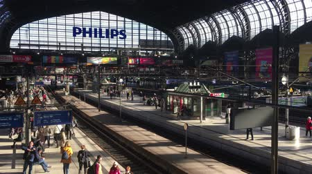 Hamburg, Germany - May 11, 2019: Wide Crane Shot of Hamburg Central Station Interior with travellers waiting for their train in sunshine  Establishing Shot