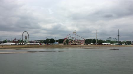 Düsseldorf - July 14, 2019: Wide Shot of large Fun Fair Rheinkirmes with Ferris Wheel, Roller Coaster, Carnival Rides filmed from the River Rhine. Its one of the largest Fun Fairs in Germany