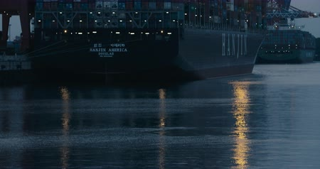 HAMBURG, AUGUST 2013: Tilt up from water onto Cargo Ship  Freighter at dusk in the port of Hamburg. Lights reflect in the water. Shot on Red.