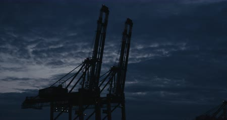 elba : HAMBURG, AUGUST 2013: Panning from big Container Cranes (Gantry Cranes) silhouetted against the evening sky to two large Container Ships in the port of Hamburg during Magic Hour (Dusk). Shot on Red. Filmati Stock