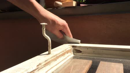 Hand using sandpaper on an old wooden window frame to apply new paint - 4K Filmati Stock