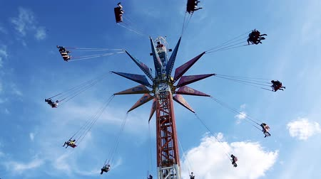 цирк : The chains carousel at blue  cloudly sky background. The happy people flying.