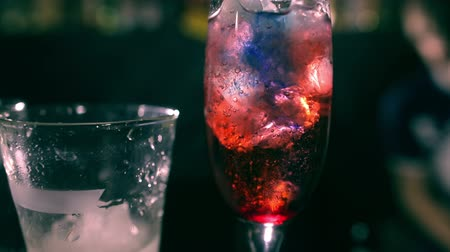 meksika : Red cocktale with ice in the bar. Deep blue syrup. Zoom in tracking pro shot with backlight