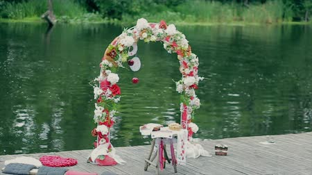 формальный : Wedding ceremony flower arch in ethnic style with river background Стоковые видеозаписи
