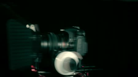 focus pull : DSLR  camera rotation. Follow focus, matte box, rig, lens on the black background. Stock Footage