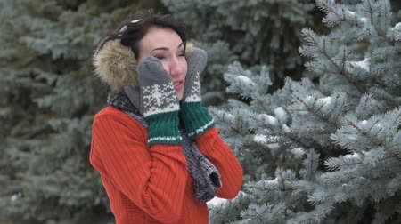 earmuffs : Woman wearing in fur mittens and earmuffs touches her face and cheeks. Winter forest. Beautiful landscape with snowy fir trees
