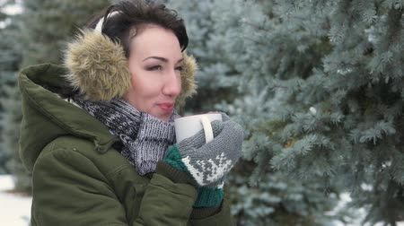 earmuffs : Woman is drinking hot tea or coffe in winter forest. She is dressed in fur earmuffs on her head. Beautiful landscape with snowy fir trees Stock Footage