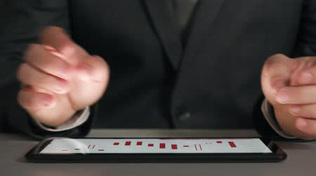 účty : Businessman working on a tablet, analyzes the graphs and tables, hands closeup. Dostupné videozáznamy